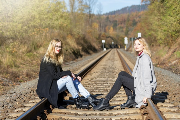 two girls are sitting on rail