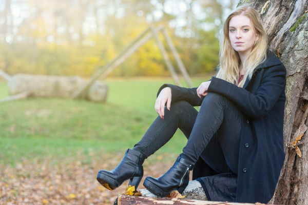 young girl is sitting in autumn