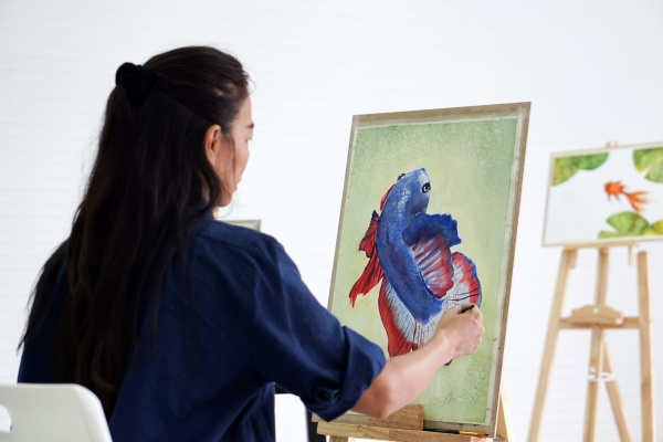 asian woman drawing a betta fighting