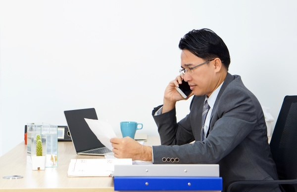 asian businessman in suit talking on