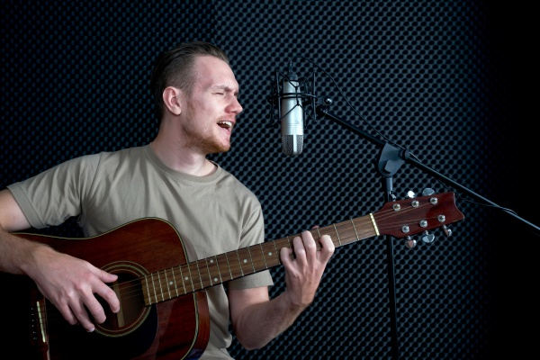 young caucasian man sings while playing