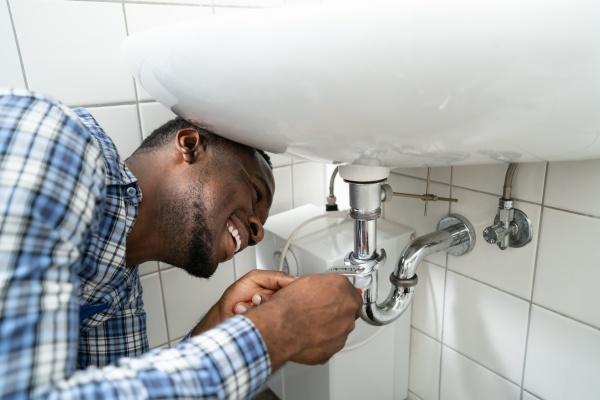 plumber fixing pipe in bathroom