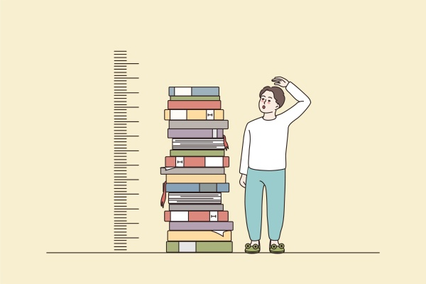 boy measuring growth stand near books