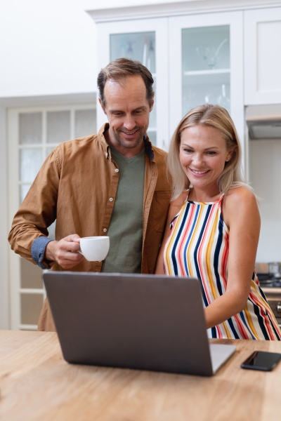 smiling caucasian couple looking at laptop