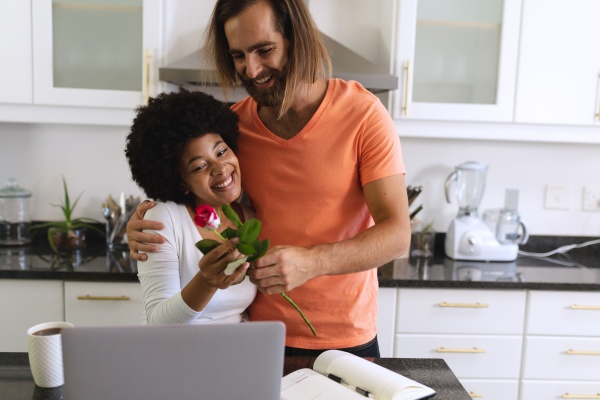 happy diverse couple sitting in kitchen
