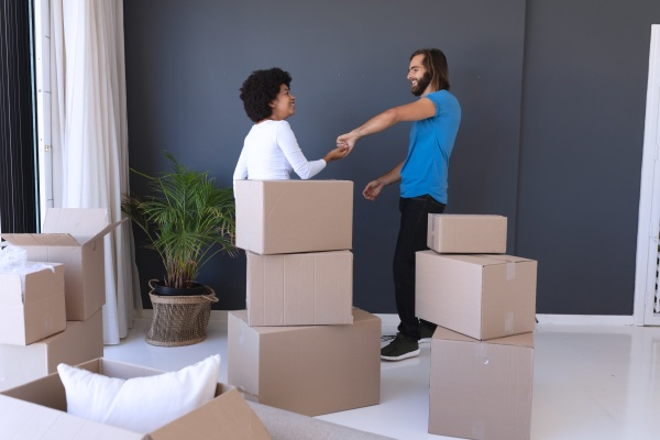 happy diverse couple moving house smiling