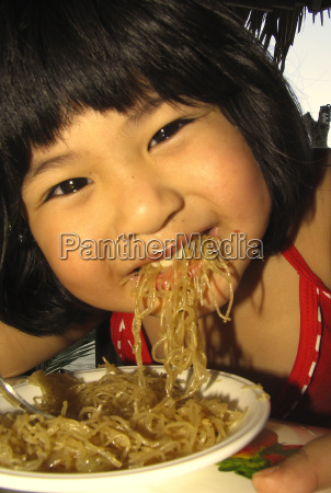 asian woman is eating a pasta