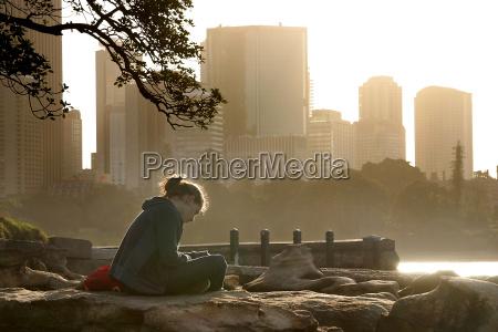 reading woman sitting on rocks in