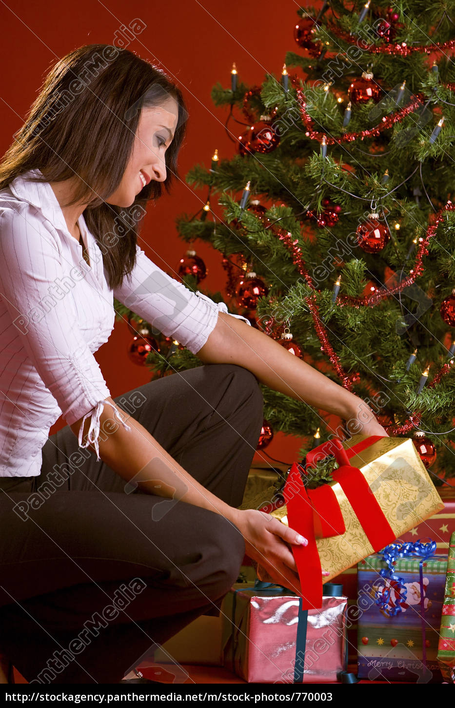 woman, puts, gift, under, christmas, tree - 770003