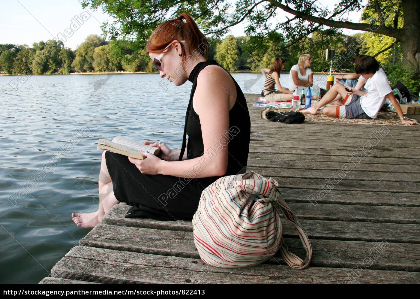 young, woman, reading, at, the, lake - 822413