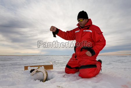 ice fisherman catching a fish on