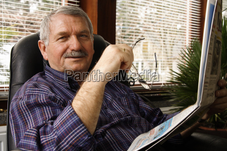 pensioner reads a newspaper