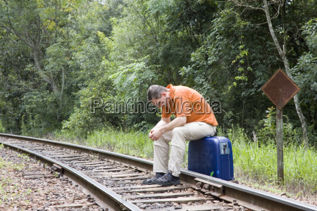 man is sitting on suitcase on