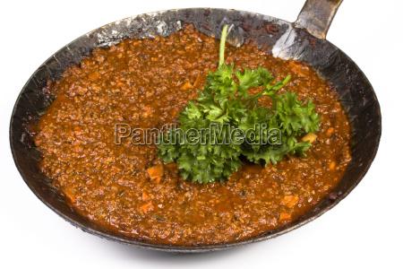 a ladle full of sauce bolognaise