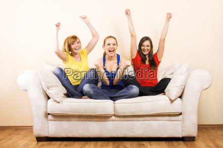 three, women, cheering, on, a, sofa - 1340637