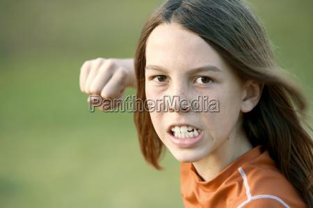 boy with long hair throws a