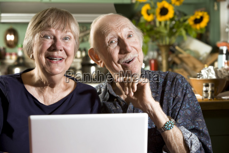 smiling senior couple with a laptop