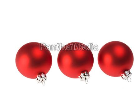 three red christmas tree balls isolated