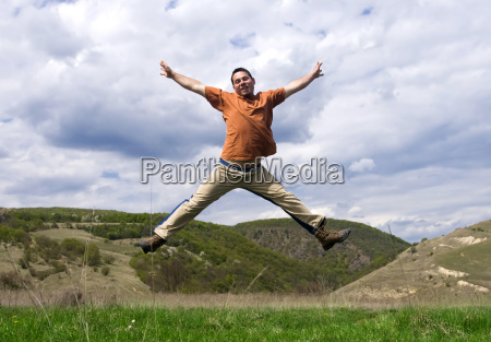 young handsome man jumping for joy