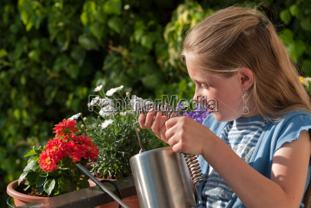 child poses balcony flowers