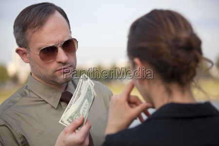 man offers money to a woman