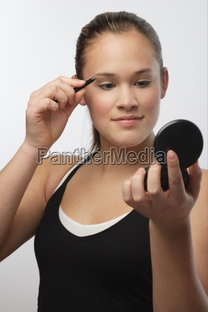 teenager with compact mirror