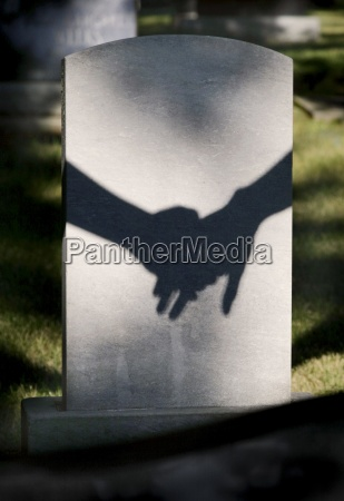 shadow on tombstone of two clasped