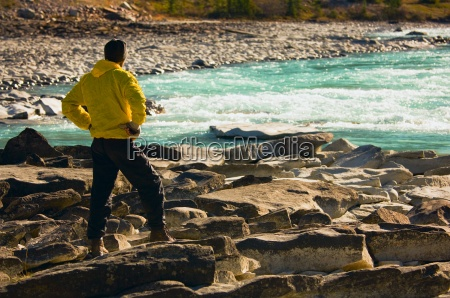 man overlooking a mountain river