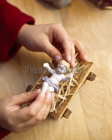 child playing with figure of baby