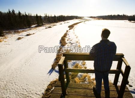 man looking at landscape from footbridge