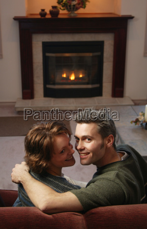 couple snuggles by fire