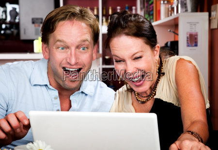 couple in coffee house with laptop