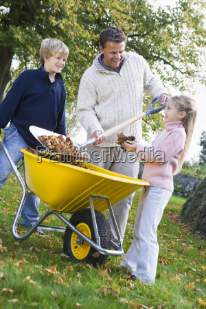 father outdoors with two young children