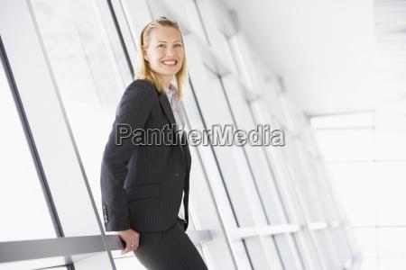 businesswoman standing in corridor smiling