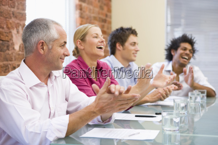 four businesspeople in boardroom applauding and