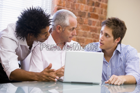 three businessmen in office with laptop