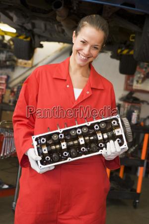 mechanic holding car part smiling