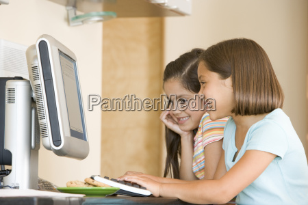 two young girls in kitchen with