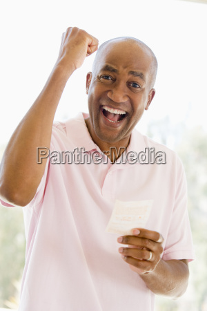 man with winning lottery ticket excited