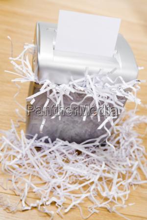 an overflowing paper shredder