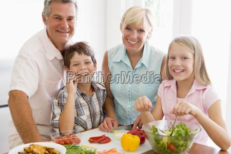 grandparents and grandchildren prepare a meal