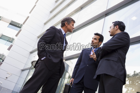 three businessmen standing outdoors by building
