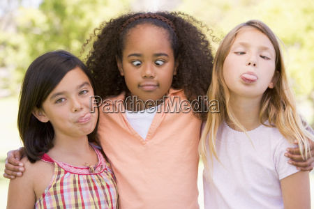 three young girl friends outdoors making