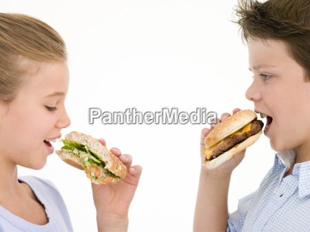 sister eating sandwich by brother eating