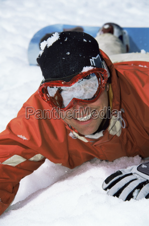 snowboarder lying on hill smiling selective