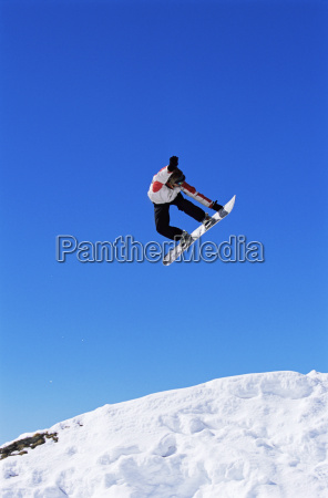 snowboarder doing jump on hill