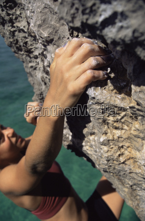 woman climbing rocks in swimwear by