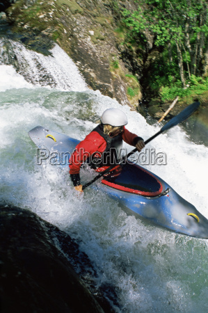 kayaker in rapids going over waterfall
