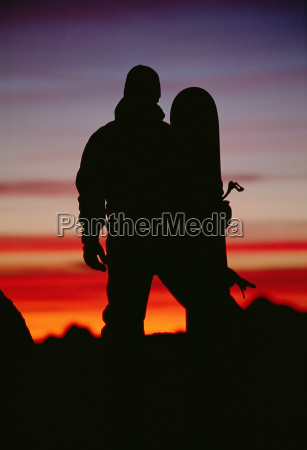 snowboarder standing outdoors at dusk silhouette