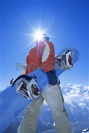 snowboarder walking on snowy hill carrying